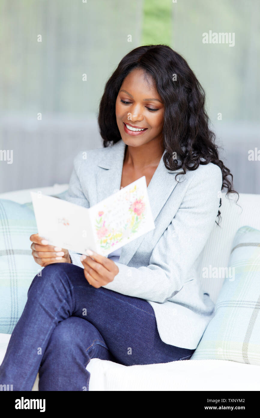 Woman reading a card - Stock Image