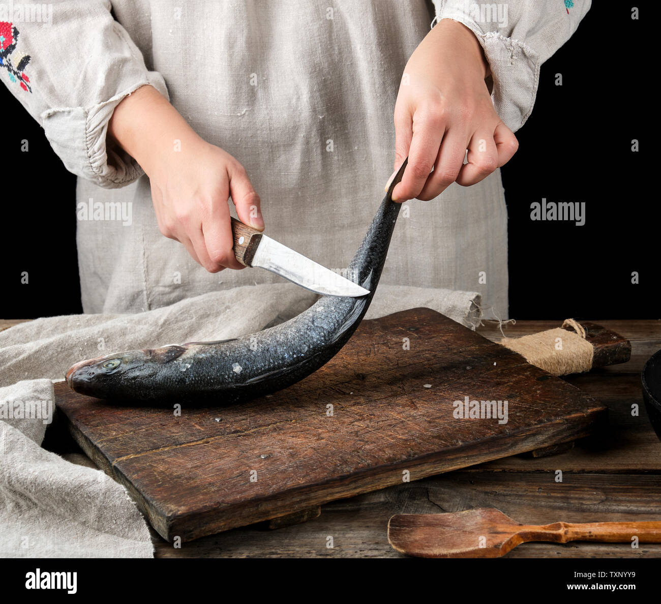 woman in gray linen clothes cleans the fish sea bass scales on a brown wooden board, black background - Stock Image
