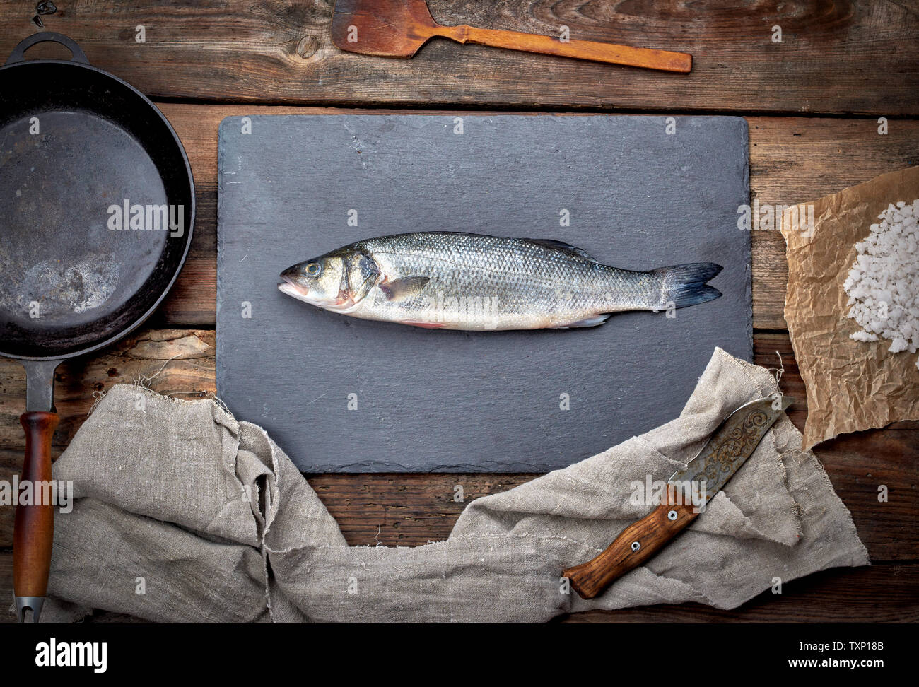 fresh whole sea bass fish on a black board, next to it is an empty round black frying pan on a wooden table, top view - Stock Image