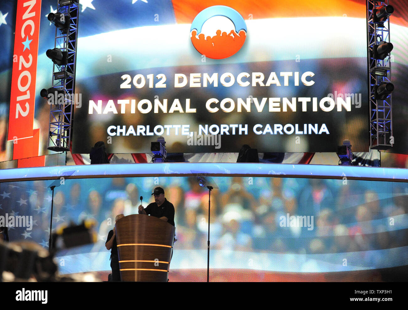 Convention stage crew members install the microphone at the