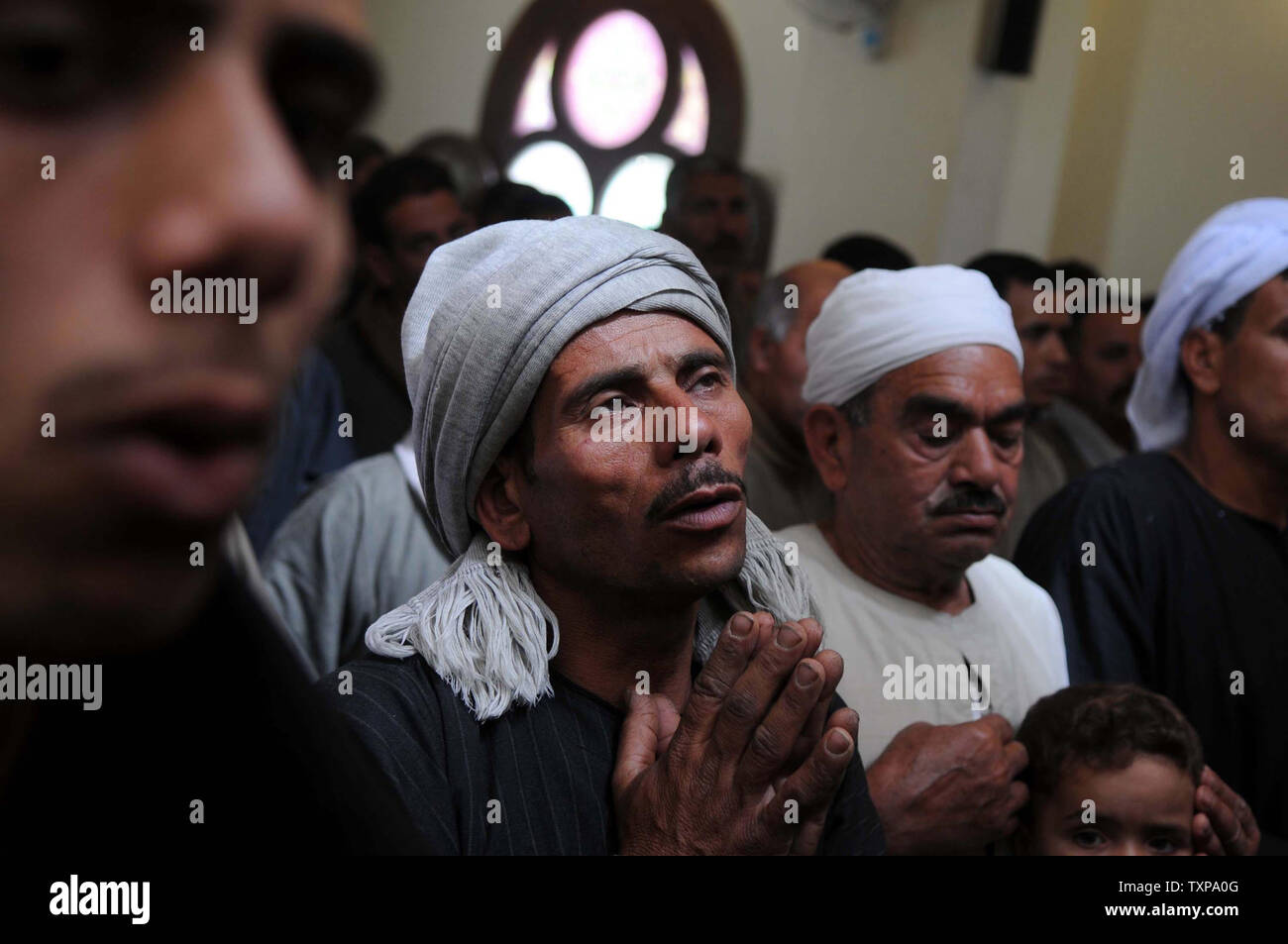 Christian Egyptian Coptics attend the first Mass in Two Martyrs Church on Sunday April 17, after it was completely rebuilt by the Egyptian army after it was torched on March 4 by angry Muslims in Helwan which is south of Cairo. Rumors of a love affair between a young Muslim woman and a Coptic man lead to the burning which triggered a large scale Coptic protest with tens of thousands gathering for several days in the center of Cairo.   UPI/Mohammed Hosam - Stock Image