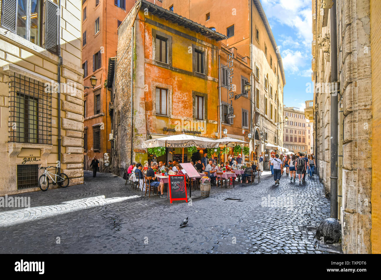 Tourists enjoy lunch on a summer day at an Italian sidewalk cafe restaurant in an alley near the historic center of Rome, Italy. Stock Photo