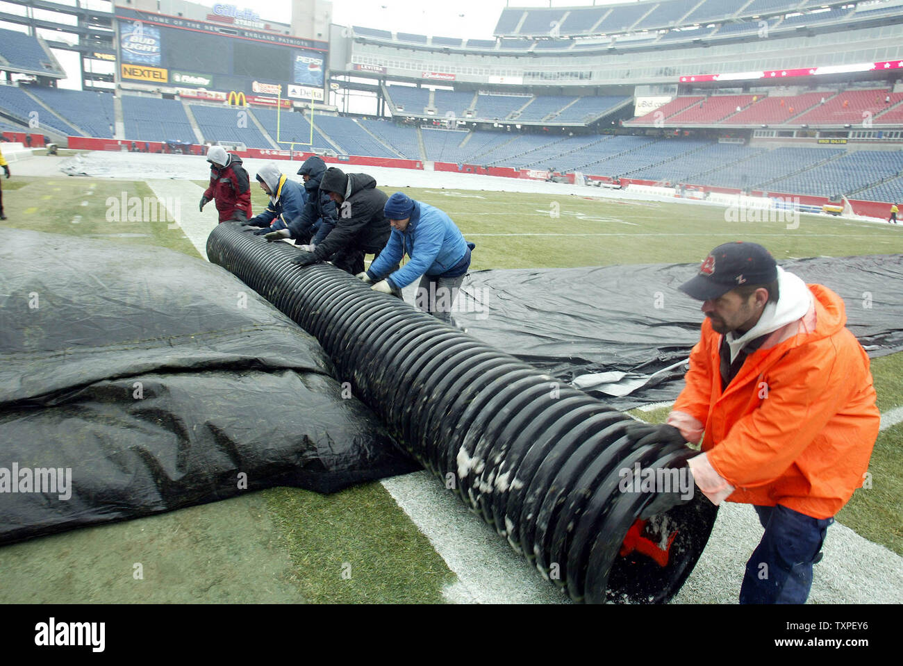 Ground crew members at Gillette Stadium remove a tarp from the field, as snow and light rain fall,  before the gates open to let fans into the Stadium for the AFC Championship Game, between the New England Patriots and Indianapolis Colts, Sunday, January 18, 2004, Foxboro, Mass, USA.  (UPI Photo / Steven E. Frischling) - Stock Image
