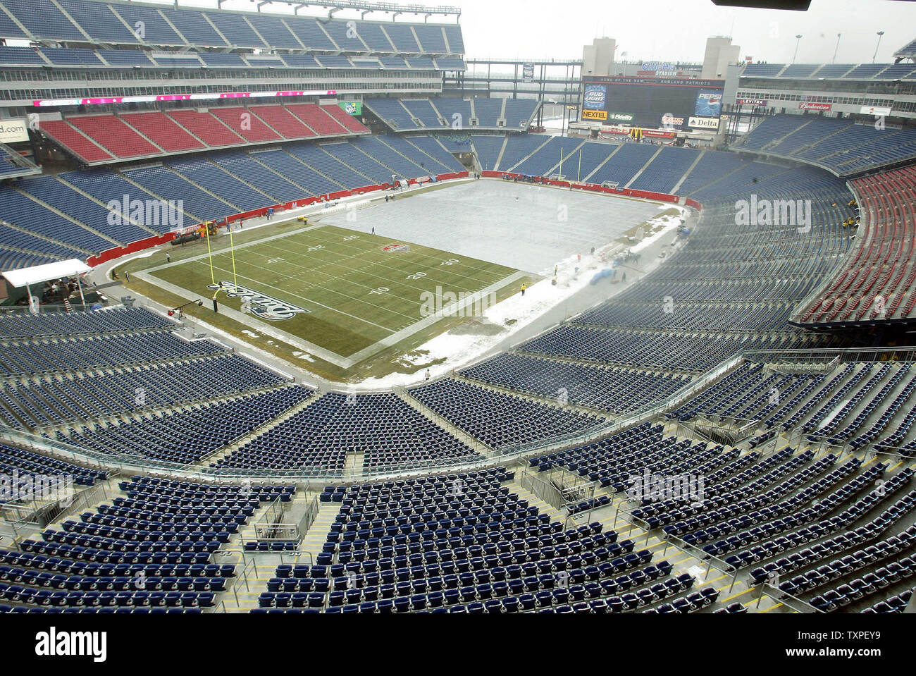 Ground crew members at Gillette Stadium remove a tarp from the west end of the field, as snow and light rain fall,  before the gates open to let fans into the Stadium for the AFC Championship Game, between the New England Patriots and Indianapolis Colts, Sunday, January 18, 2004, Foxboro, Mass, USA.  (UPI Photo / Steven E. Frischling) - Stock Image