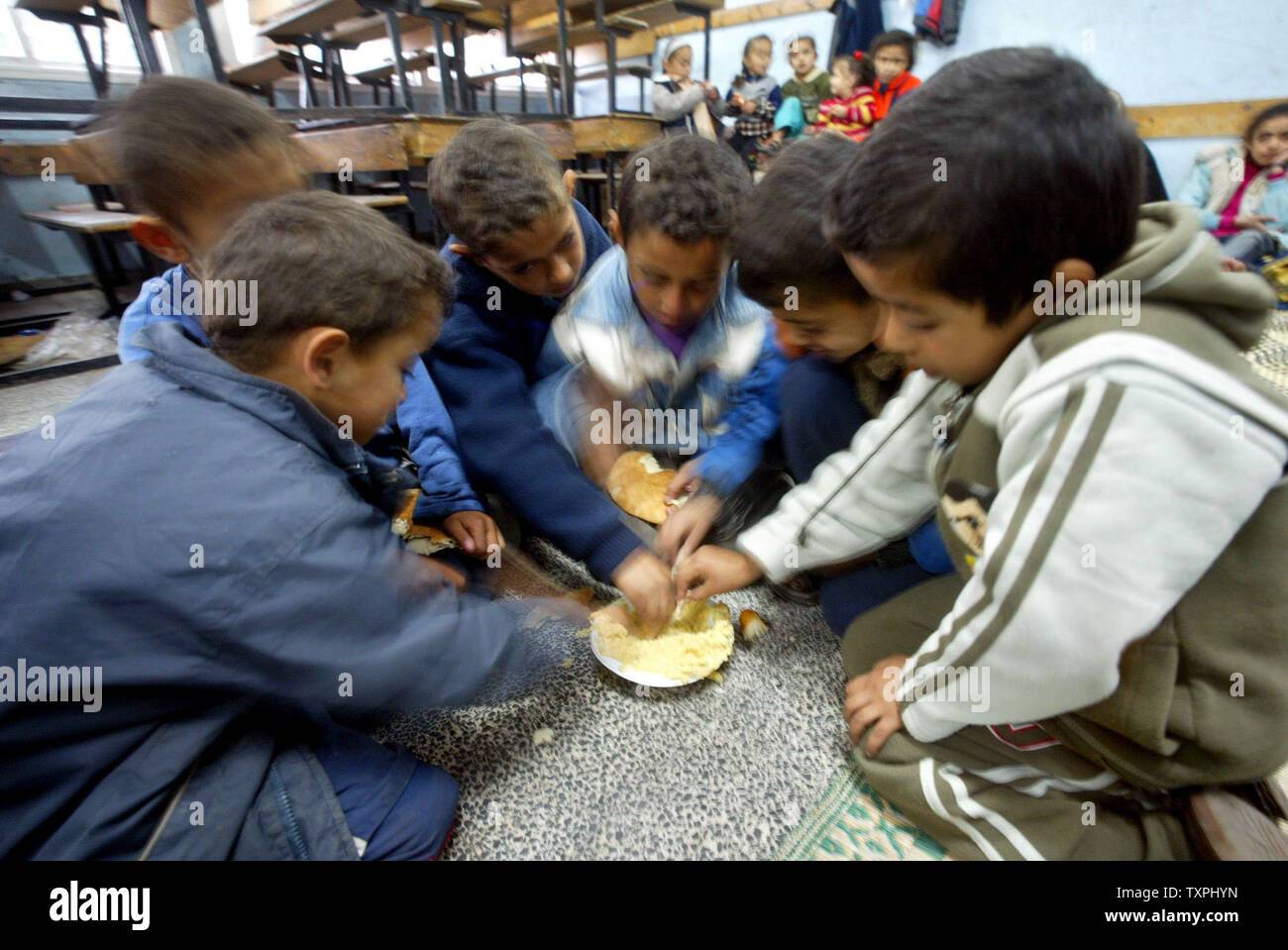 Palestinian  children eat inside a UN school after the demolishing of their homes by Israel in the southern Gaza Strip refugee camp of Rafah on  December 18, 2004. The Palestinian death toll during a large-scale Israeli incursion in the southern Gaza Strip rose to 11, Palestinian medical sources said.  (UPI Photo /Ismael Mohamad) - Stock Image