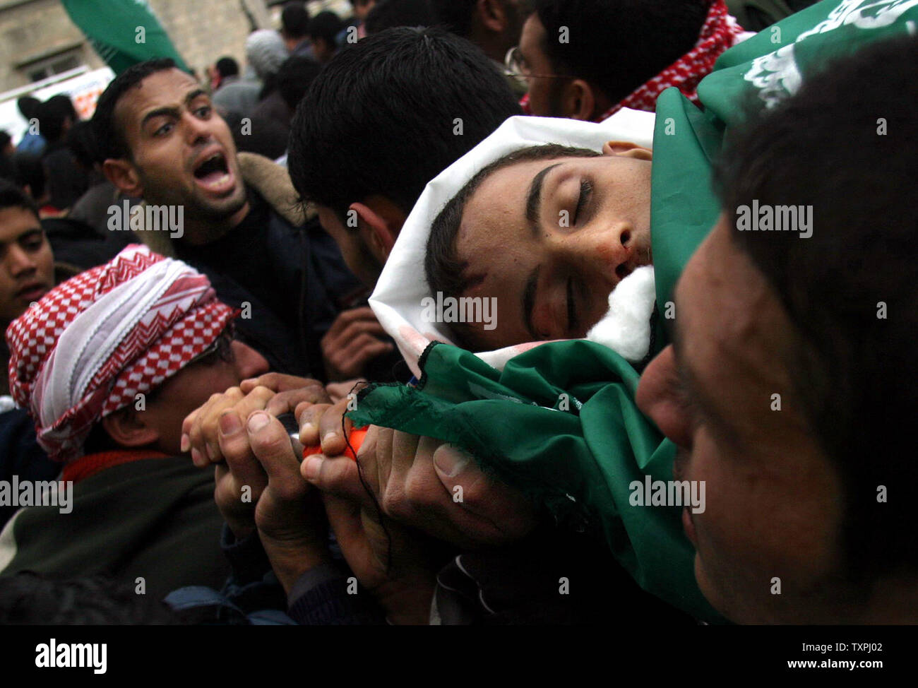 Relatives of 19 year-old Palestinian Jihad Abu Omar mourn during his funeral in the Khan Younis refugee camp in the Gaza Strip on December 18, 2004. According to Palestinian medical sources, Omar was the sixth Palestinian killed in camp since the start of a large-scale Israeli incursion.  (UPI Photo /Ismael Mohamad) - Stock Image