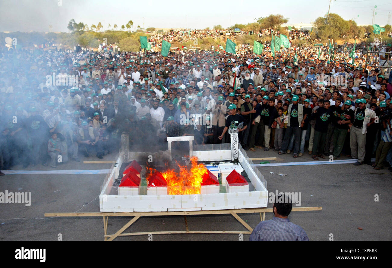 Hamas supporters burn a scale model of a Jewish settlement in Neve Dekalim, during a rally celebrating the Israeli withdrawal from Gaza in the evacuated Jewish settlement of Neve Dekalim, in the southern Gaza Strip, Friday, Sept. 16, 2005.  (UPI Photo /Ismael Mohamad) - Stock Image