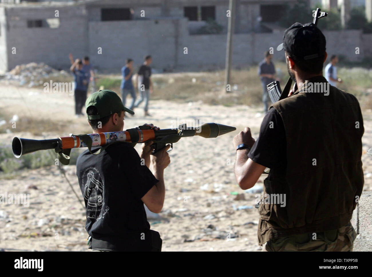 Palestinian fighters hold their guns as they face off with an Israeli tank during clashes in Beit Lahia, northern Gaza Strip on July 6, 2006. Israeli infantry and armor launched a large-scale operation into the northern Gaza Strip in the early morning, effectively establishing a new buffer zone in an attempt to prevent the launch of improved Palestinian Qassam rockets which have struck downtown Ashkelon in the past few days.  (UPI Photo/Ismael Mohamad) - Stock Image