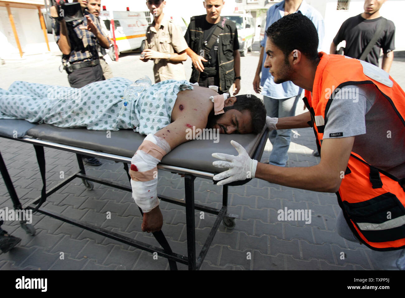 A Palestinian ambulance worker wheels a man wounded by Israeli troops in Beit Lahia, northern Gaza Strip on July 6, 2006. Israeli infantry and armor launched a large-scale operation into the northern Gaza Strip in the early morning, effectively establishing a new buffer zone in an attempt to prevent the launch of improved Palestinian Qassam rockets which have struck downtown Ashkelon in the past few days.  (UPI Photo/Ismael Mohamad) - Stock Image