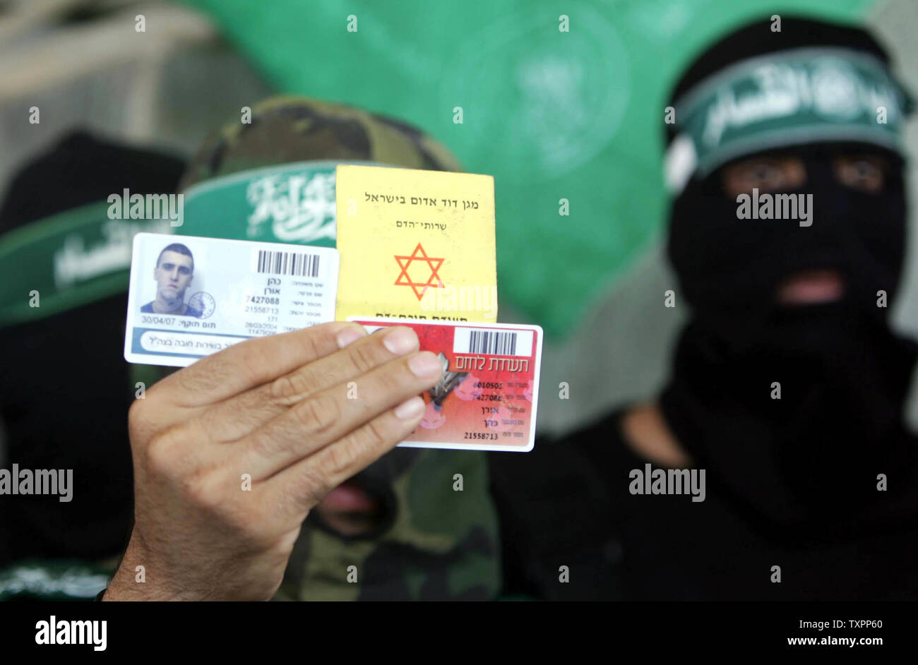 Abu Obayda, the spokesman of the military wing of Hamas the Ezz El-Deen Al-Qassam Brigades, displays the ID cards of Israeli soldiers left them behind when Israeli tanks withdrew in Beit Lahia, northern Gaza, on July 8, 2006. According to sources Israel has pulled out its forces from the town of Beit Lahia following the death of 35 Palestinians and one Israeli soldier since Israel launched a large scale military operation in Gaza this week aimed at preventing rocket attacks and securing the release of a captured soldier.  (UPI Photo/Ismael Mohamad) - Stock Image