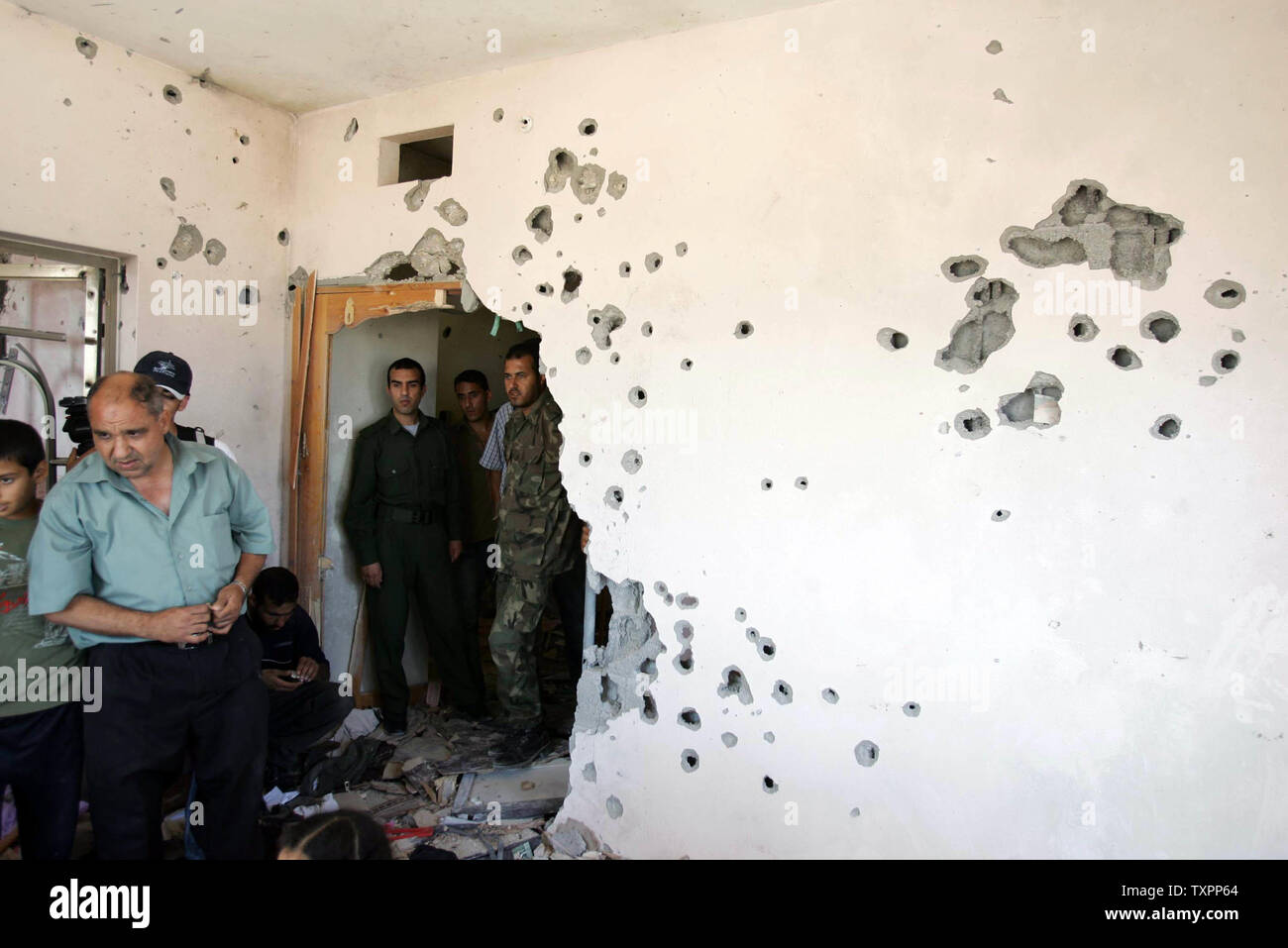 Palestinians survey a house damaged by Israeli tank bullets in Beit Lahia, northern Gaza Strip on July 8, 2006. According to sources Israel has pulled out its forces from the town of Beit Lahia following the death of 35 Palestinians and one Israeli soldier since Israel launched a large scale military operation in Gaza this week aimed at preventing rocket attacks and securing the release of a captured soldier.  (UPI Photo/Ismael Mohamad) - Stock Image