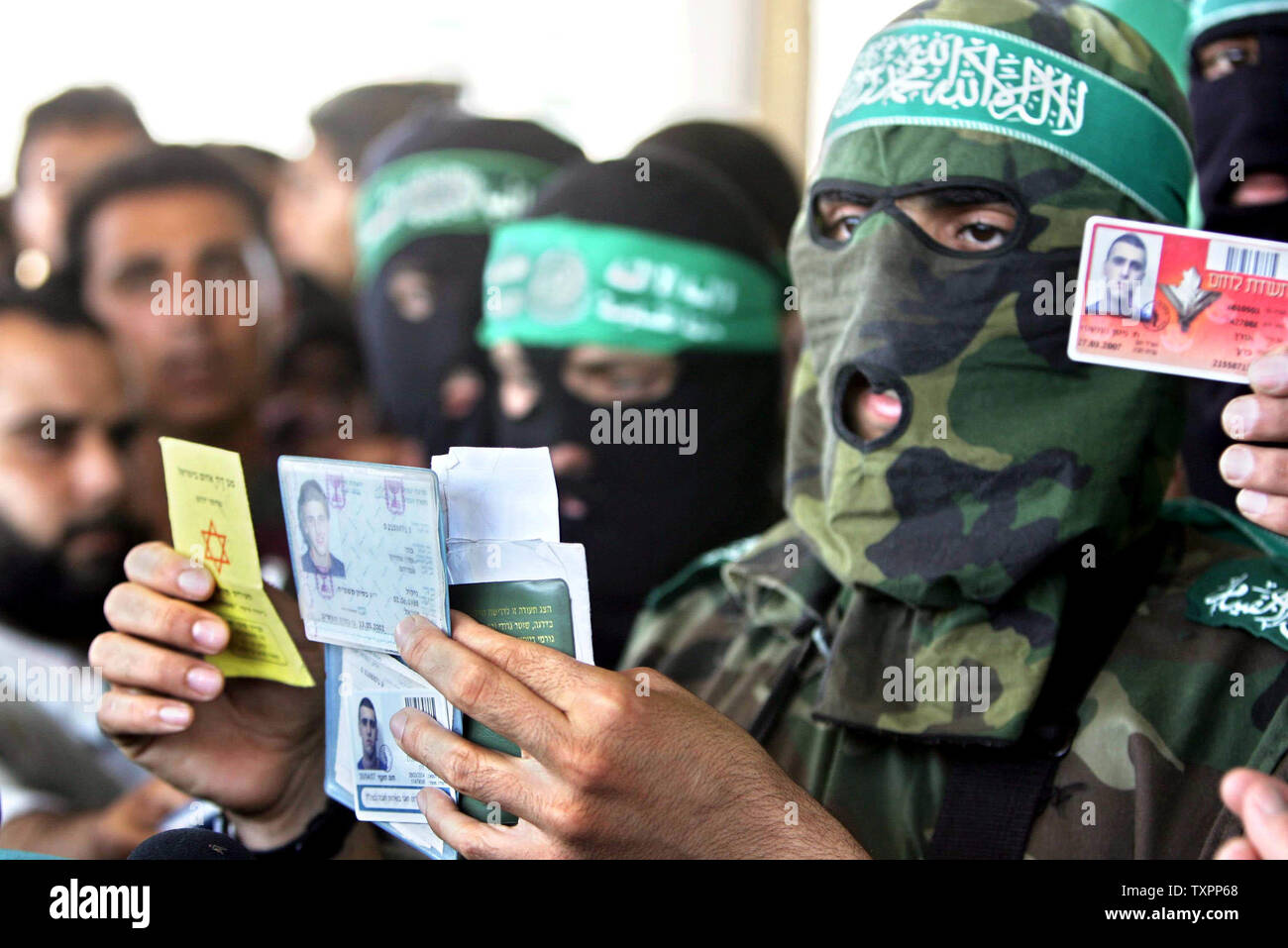 Abu Obayda, the spokesman of the military wing of Hamas the Ezz El-Deen Al-Qassam Brigades, displays the ID cards of Israeli soldiers left them behind when Israeli tanks withdrew in Beit Lahia, northern Gaza, on July 8, 2006. According to sources, Israel has pulled out its forces from the town of Beit Lahia following the death of 35 Palestinians and one Israeli soldier since Israel launched a large scale military operation in Gaza this week aimed at preventing rocket attacks and securing the release of a captured soldier.  (UPI Photo/Ismael Mohamad) - Stock Image