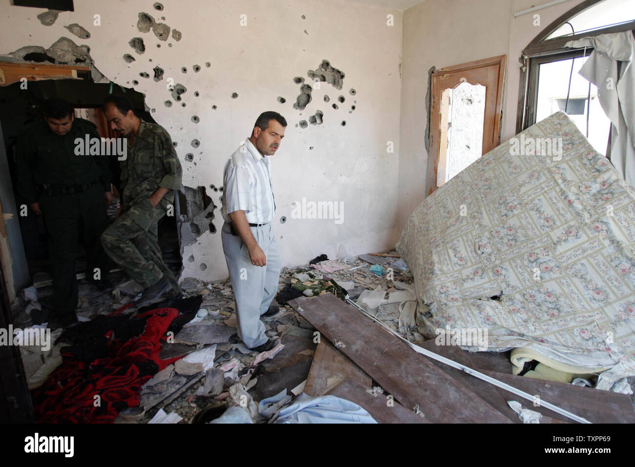 A Palestinian family surveys the damage in a bedroom destroyed by Israeli tanks and bullets in Beit Lahia, northern Gaza, on July 8, 2006. According to sources, Israel has pulled out its forces from the town of Beit Lahia following the death of 35 Palestinians and one Israeli soldier since Israel launched its large scale military operation in Gaza this week aimed at preventing rocket attacks and securing the release of a captured soldier.  (UPI Photo/Ismael Mohamad) - Stock Image