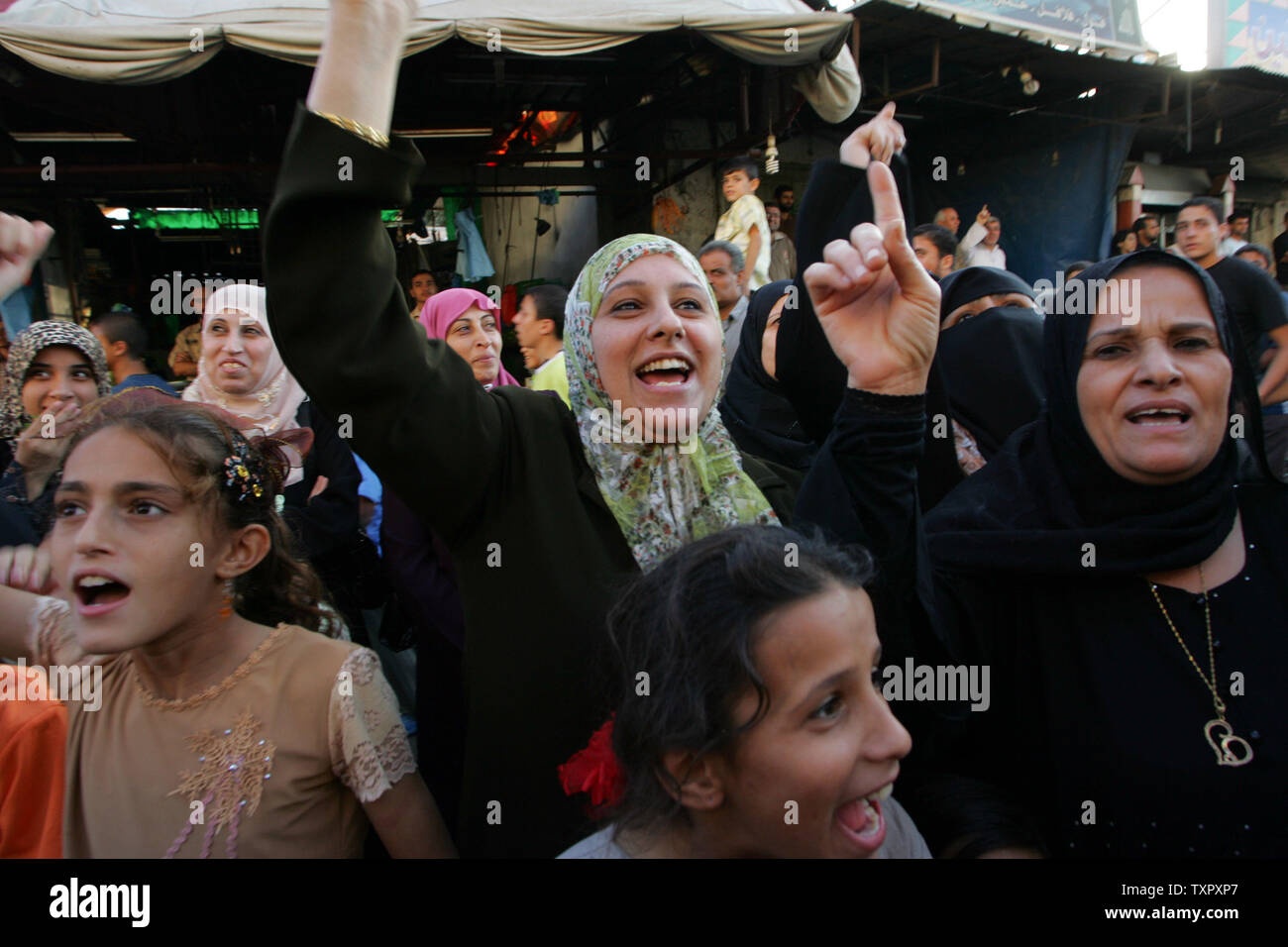 Palestinian women supporters of Hamas shout as militants from the Islamic group Hamas march past during a rally organized by the Hamas movement in Nuseirat, southern Gaza on October 17, 2008. (UPI Photo/Ismael Mohamad) - Stock Image