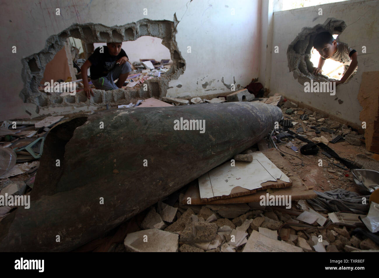A Palestinian boys looks at a missile which witnesses said was fired by Israeli aircraft, in their flat in the destroyed Nada Towers During Cease-Fire between Gaza and Israel,  in the town of Beit Lahiya, northern Gaza Strip, August. 12, 2014. UPI/Ismael Mohamad Stock Photo