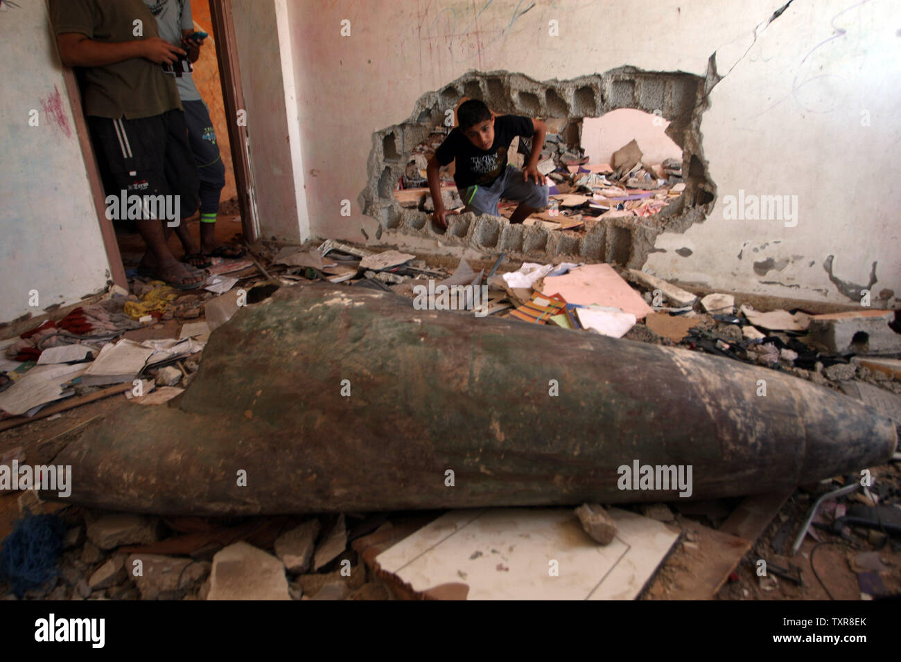 A Palestinian boy looks at a missile which witnesses said was fired by Israeli aircraft, in his flat in the destroyed Nada Towers During Cease-Fire between Gaza and Israel,  in the town of Beit Lahiya, northern Gaza Strip, August. 12, 2014. UPI/Ismael Mohamad Stock Photo