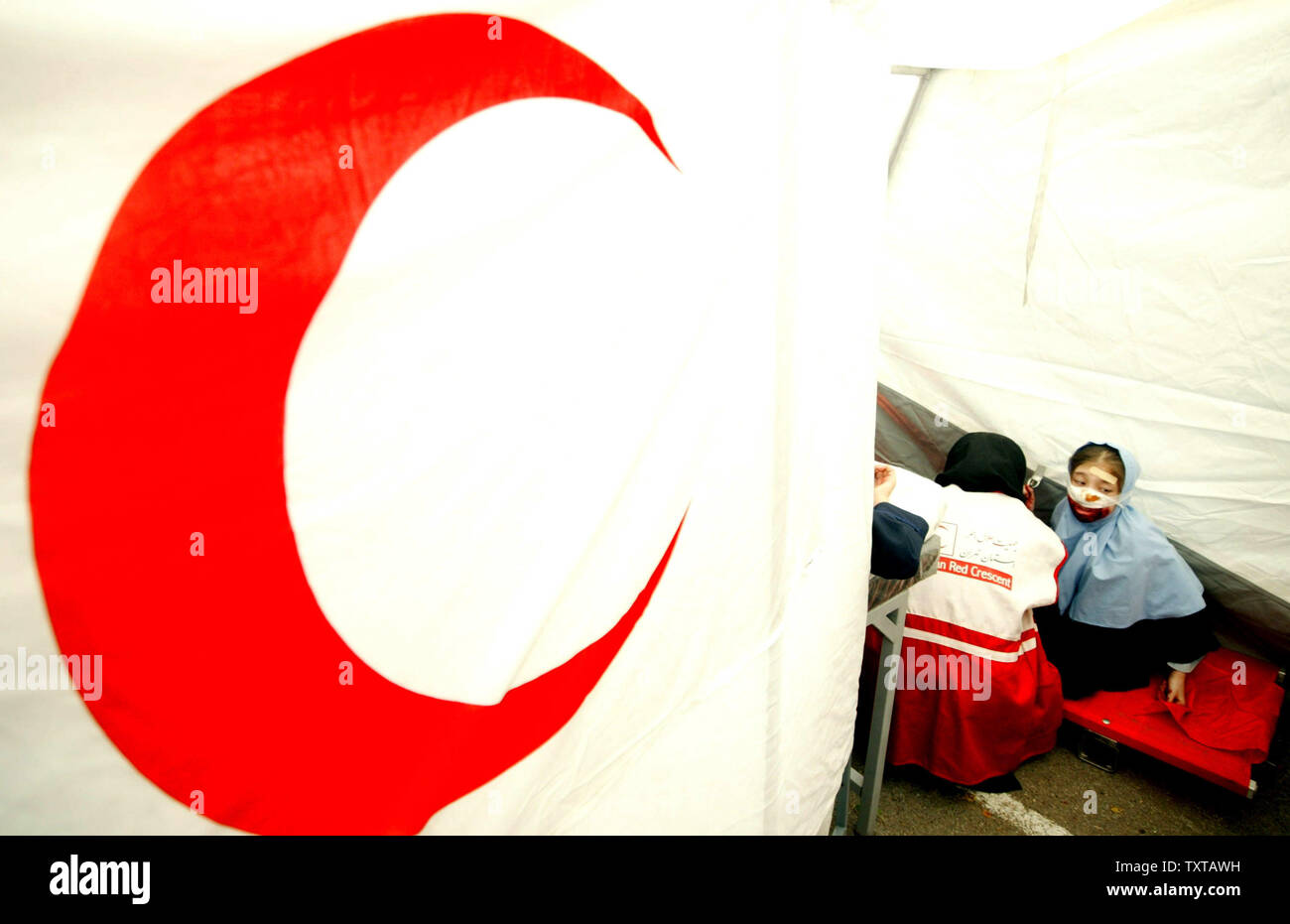 Iranian students treat a wounded student in a Red Crescent station during an earthquake drill in one of the schools in Tehran, Iran on  November 29, 2005.  This is the 7th drill in a series to help prepare students in this seismically active country. (UPI Photo/Mohammad Kheirkhah) - Stock Image