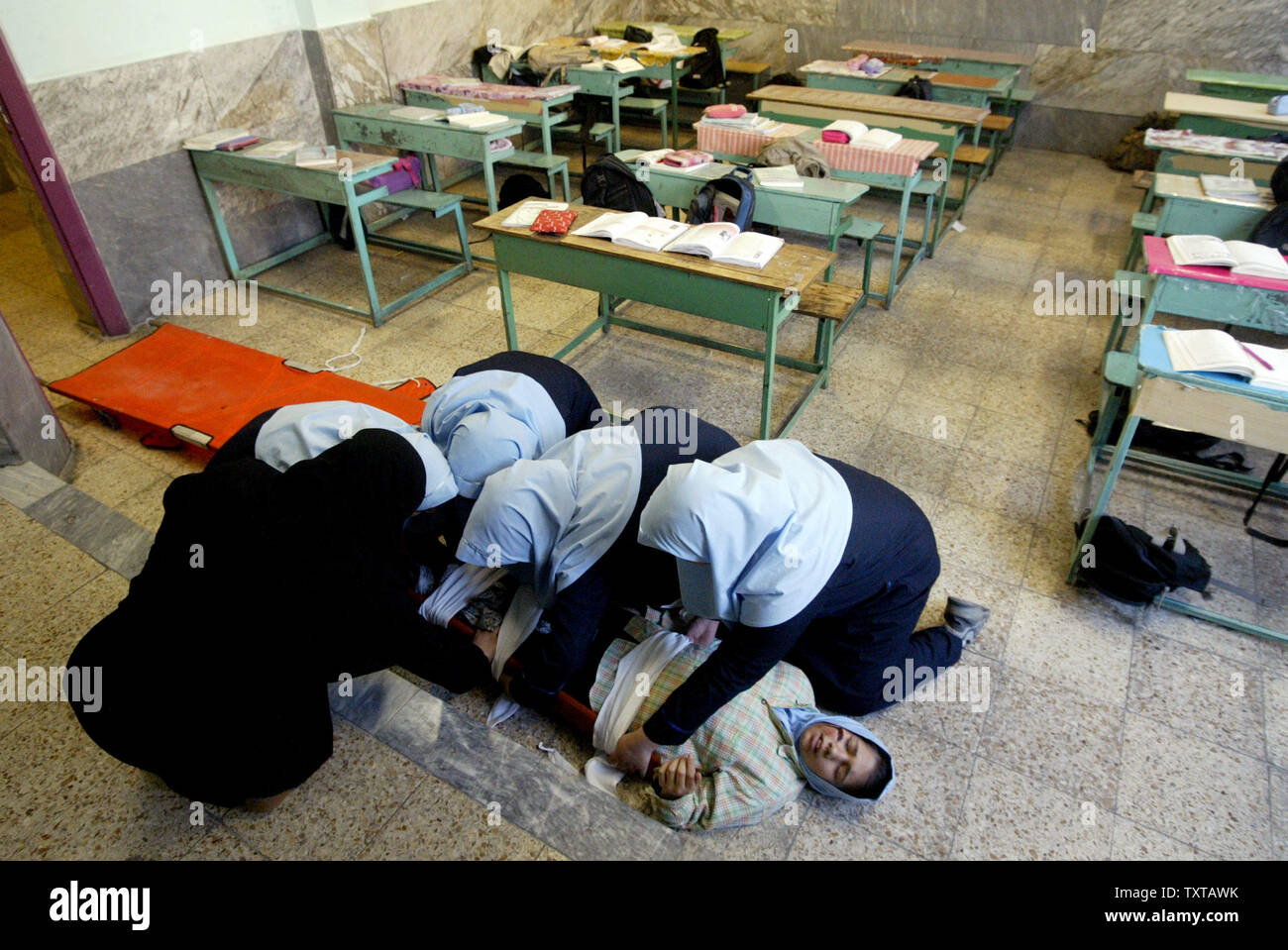 Iranian students treat a wounded student during an earthquake drill in one of the schools in Tehran, Iran on November 29, 2005. This is the 7th drill in a series to help prepare students in this seismically active country. (UPI Photo/Mohammad Kheirkhah) - Stock Image