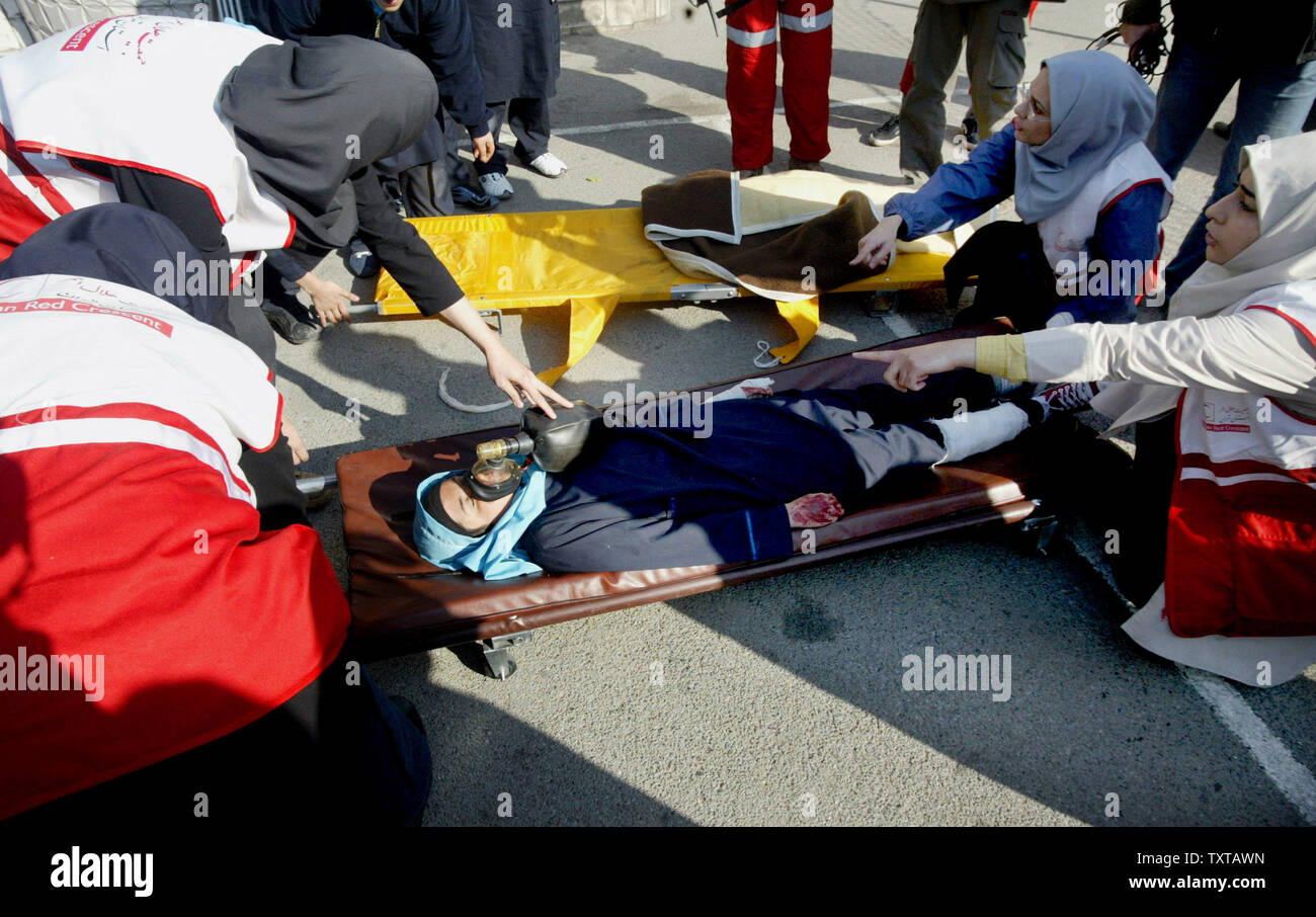 Iranian students treat a supposedly wounded student during an earthquake drill in one of the schools in Tehran, Iran on November 29, 2005. This is the 7th drill in a series to help prepare students in this seismically active country. (UPI Photo/Mohammad Kheirkhah) - Stock Image