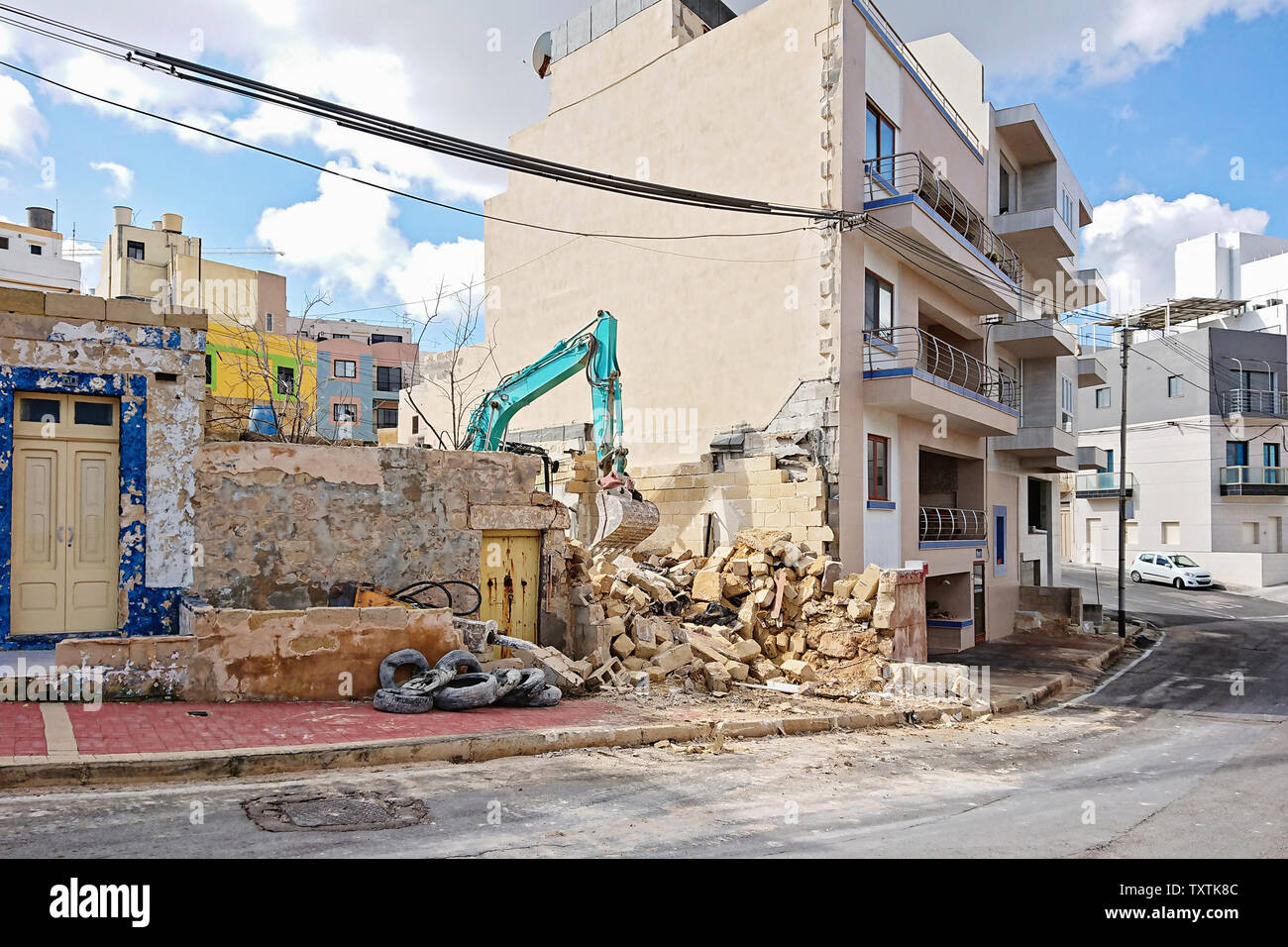 Excavator working at the demolition of an old residential building among other houses. Excavation and demolition works Stock Photo