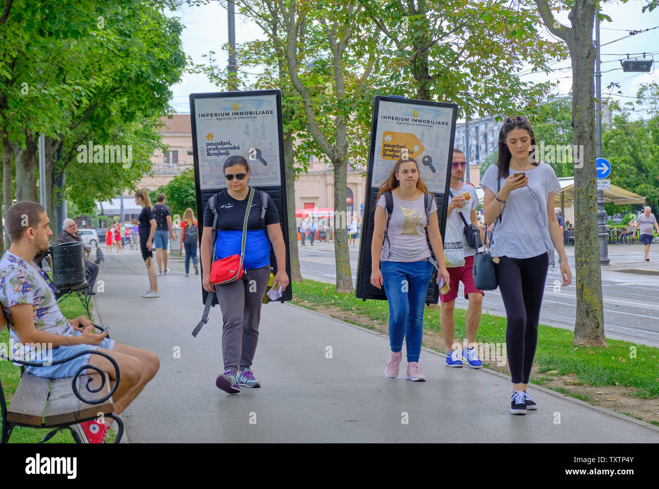 Two young females carrying walking advertizing billboard on their shoulders walking on sidewalks while man watches. Zagreb, Croatia - June 22, 2019. - Stock Image