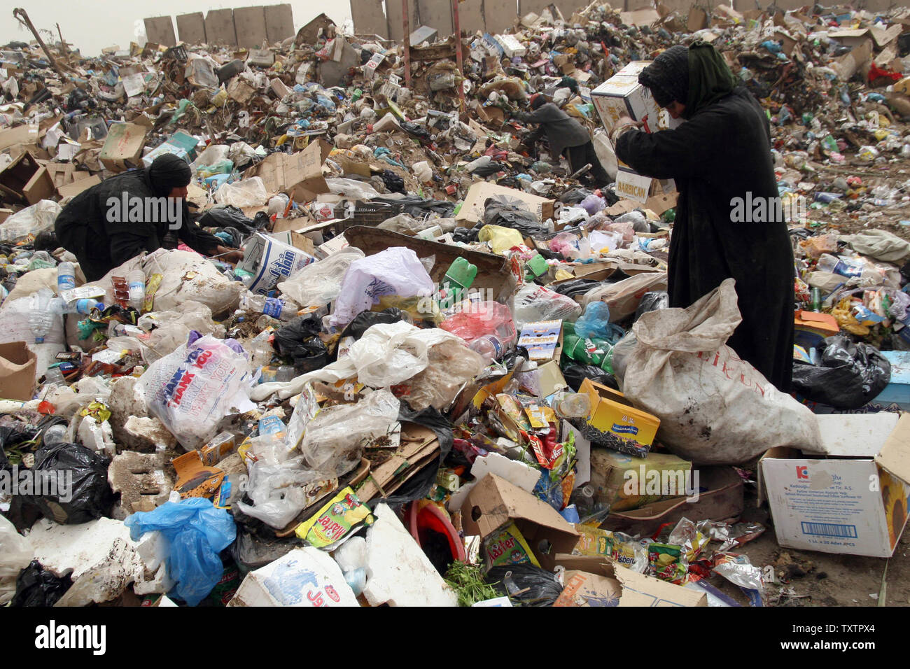 Iraqis rummage through piles of garbage at a dump in Baghdad on March 28, 2009. The worsening economic situation in Iraq and the lack of jobs has forced many Iraqi families to spend their days looking for metal and other recyclable items to resell. (UPI Photo/Ali Jasim) - Stock Image
