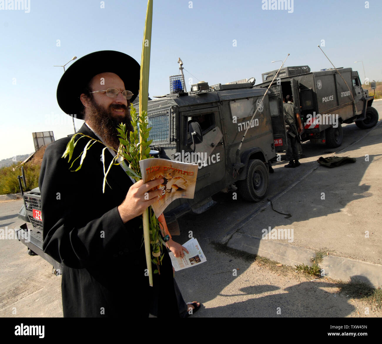 An Ultra-Orthodox Jew carries lulav for Sukkot past Israeli border police jeeps in the Jewish settlement Efrat in the West Bank, September 30, 2007.  (UPI Photo/ Debbie Hill) - Stock Image