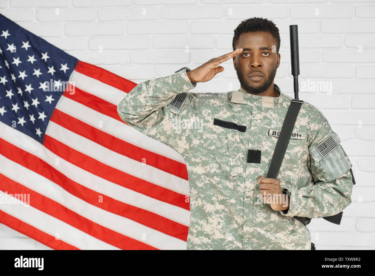 Young serious ranker standing near American flag and holding hand near head, ready for army. Soldier wearing green uniform holding weapon on back and looking at camera. Concept of preparing for army. - Stock Image