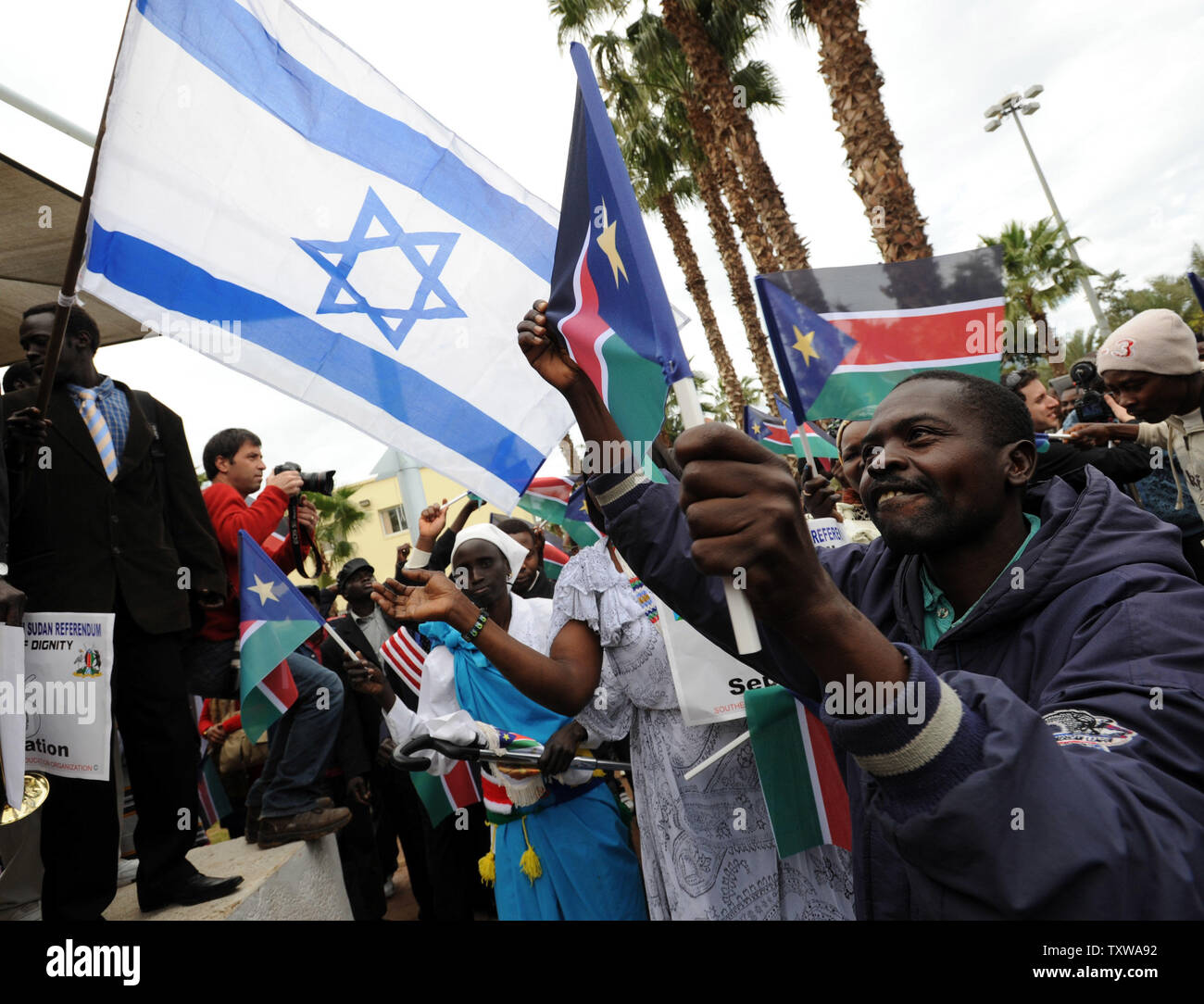 South Sudanese refugees wave South Sudan and Israeli flags at a rally in Tel Aviv, Israel, to support the Southern Sudan referendum, January 9, 2011. More than a million Southern Sudanese started casting their ballots in the seven day referendum that would split Christian South Sudan from the northern government dominated by Arab Muslims. The referendum is expected to split Africa's largest nation into two, giving birth to the world's newest nation. UPI/Debbie Hill - Stock Image