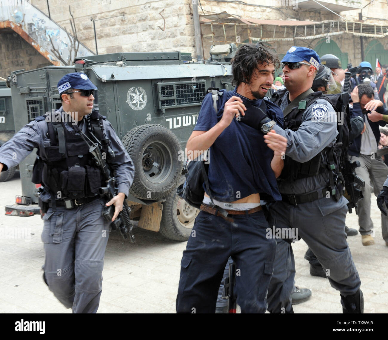 Israeli riot police arrest a left-wing activist during a protest against the closure of Shuhada Street to Palestinians in Hebron, West Bank, February 25, 2011. Demonstrators shouted slogans against the U.S. for vetoing the UN Security Council resolution condemning Israeli settlements.  UPI/Debbie Hill. - Stock Image
