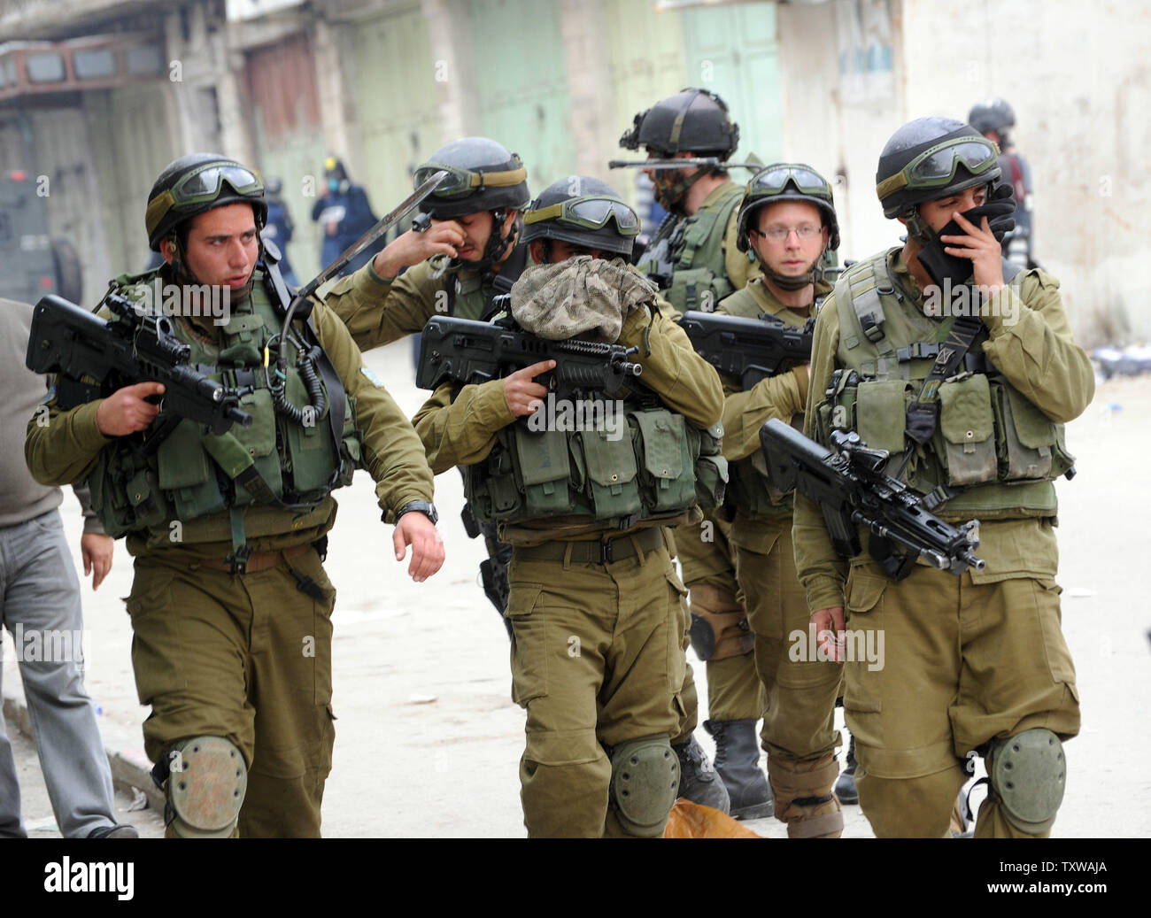 Israeli soldiers cover their faces after firing tear gas at  Palestinian and international activists during a protest against the closure of Shuhada Street to Palestinians in Hebron, West Bank, February 25, 2011. Demonstrators shouted slogans against the U.S. for vetoing the UN Security Council resolution condemning Israeli settlements.  UPI/Debbie Hill. - Stock Image