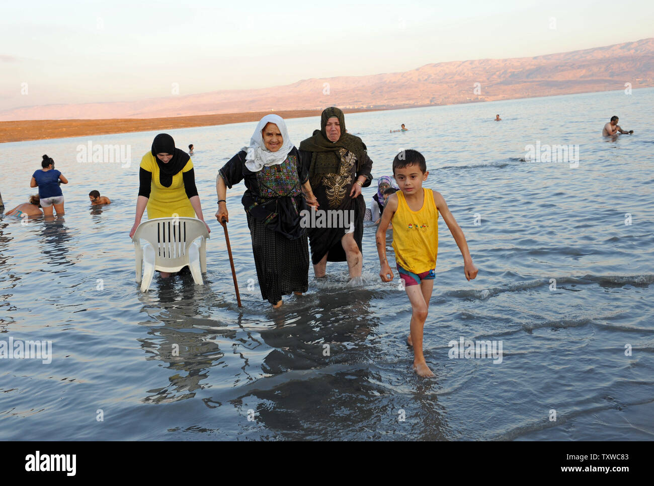Palestinians walk out of the Dead Sea at Kalya Beach, West Bank, on the second day of the  Muslim festival Eid al-Adha, November 7, 2011. The Dead Sea is among the top 10 finalists in the International New 7 Wonders of Nature Campaign, which will conclude on Friday, 11.11.11.  UPI/Debbie Hill Stock Photo