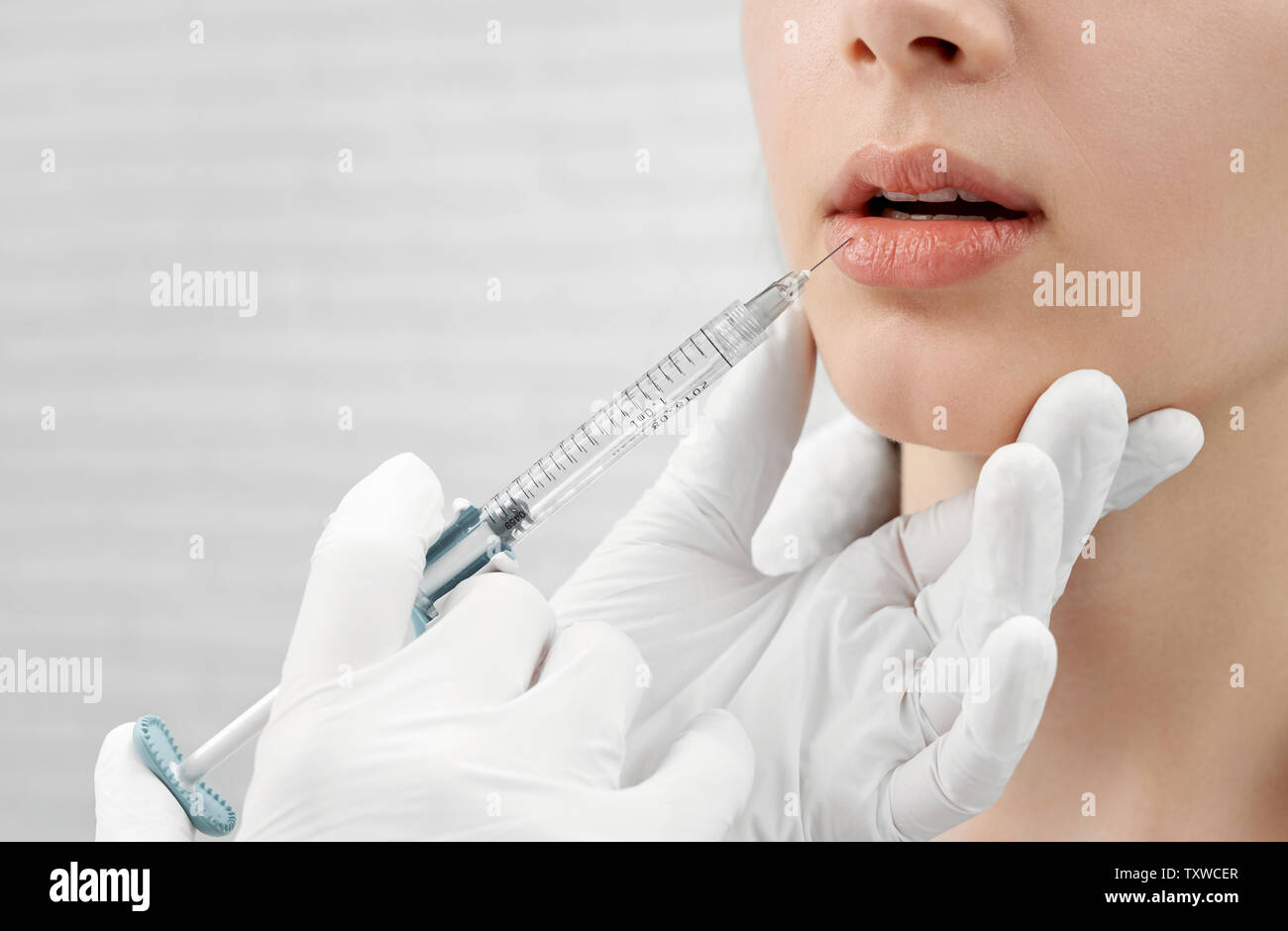 Close up of hands in white rubber medical gloves making injection, holding syringe, touching female chin. Well groomed face of young woman receiving botox of lips. Concept of beauty. Stock Photo