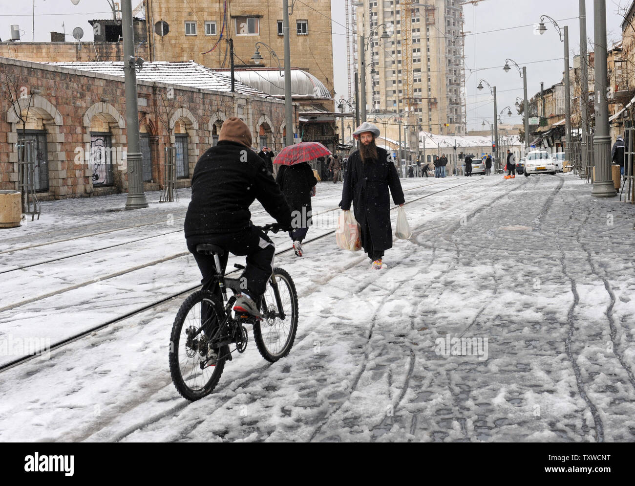 Israelis walk in a rare winter snow storm on Jaffa Road in central Jerusalem, March 2, 2012. Residents of Jerusalem woke to 1.575 inches of snow in the first snow fall in Jerusalem in more than two years.  UPI/Debbie Hill - Stock Image