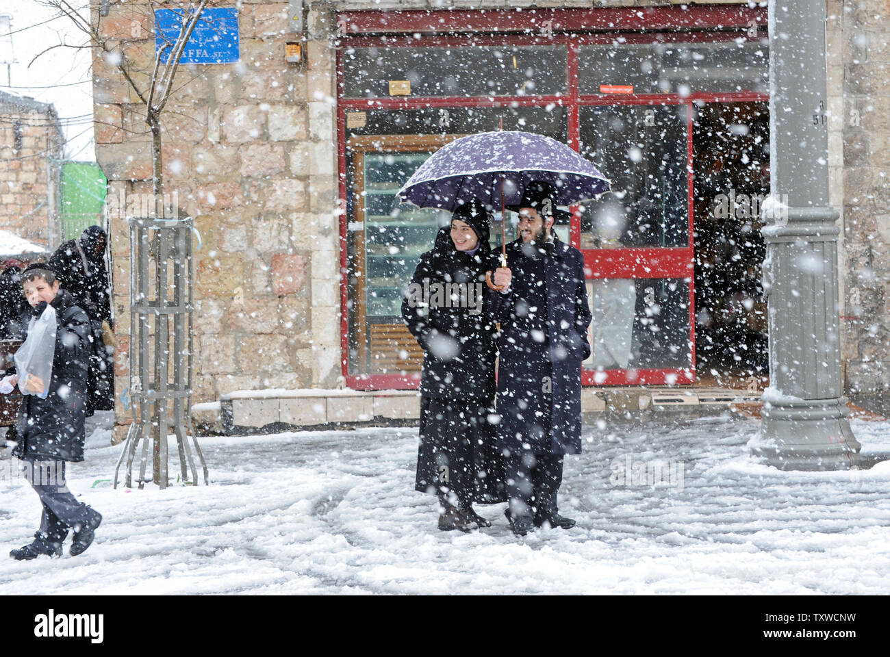 An Ultra-Orthodox Israeli couple takes cover under an umbrella during a rare winter snow storm on Jaffa Road in central Jerusalem, March 2, 2012. Residents of Jerusalem woke to 1.575 inches of snow in the first snow fall in Jerusalem in more than two years.  UPI/Debbie Hill - Stock Image