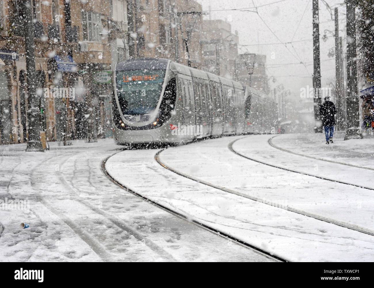 The light rail train runs on Jaffa Road in central Jerusalem during a rare winter snow storm, March 2, 2012. Residents of Jerusalem woke to 1.575 inches of snow in the first snow fall in Jerusalem in more than two years.  UPI/Debbie Hill - Stock Image
