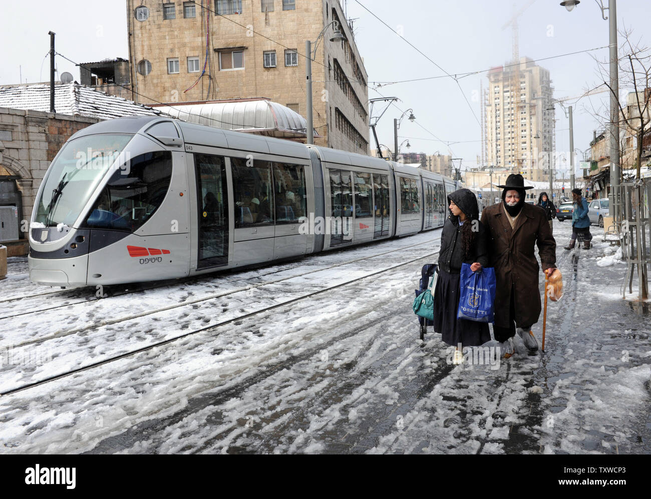 The Jerusalem light rail train passes Israelis walking in a rare winter snow storm on Jaffa Road in central Jerusalem, March 2, 2012. Residents of Jerusalem woke to 1.575 inches of snow in the first snow fall in Jerusalem in more than two years.  UPI/Debbie Hill - Stock Image