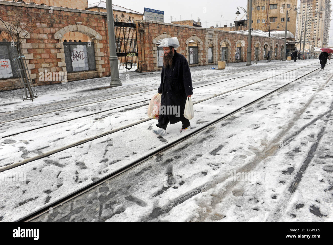 An Ultra-Orthodox Israeli walks with plastic bags on his shoes and hat during a rare winter snow storm on Jaffa Road in central Jerusalem, March 2, 2012. Residents of Jerusalem woke to 1.575 inches of snow in the first snow fall in Jerusalem in more than two years.  UPI/Debbie Hill - Stock Image