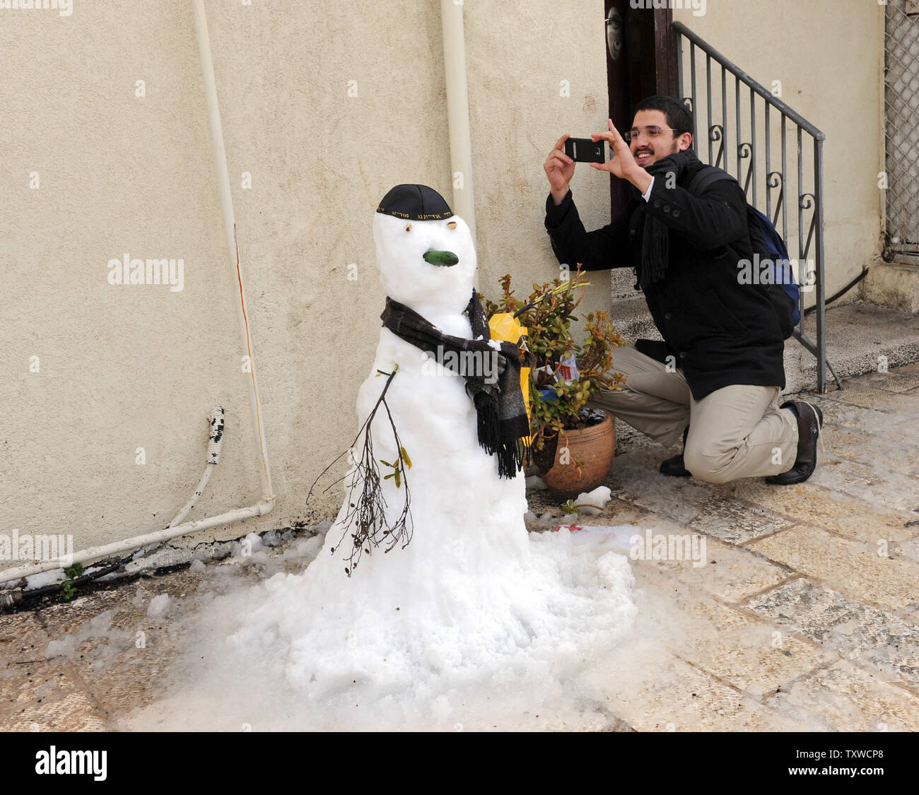 An Israeli takes a photo of a snow man after a rare winter snow storm in Jerusalem, March 2, 2012. Residents of Jerusalem woke to 1.575 inches of snow in the first snow fall in Jerusalem in more than two years.  UPI/Debbie Hill - Stock Image