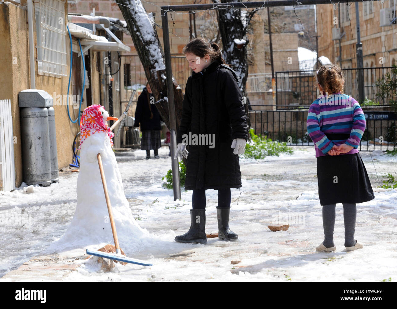 An Israeli girl builds a snow man during a rare winter snow storm in Jerusalem, March 2, 2012. Residents of Jerusalem woke to 1.575 inches of snow in the first snow fall in Jerusalem in more than two years.  UPI/Debbie Hill - Stock Image