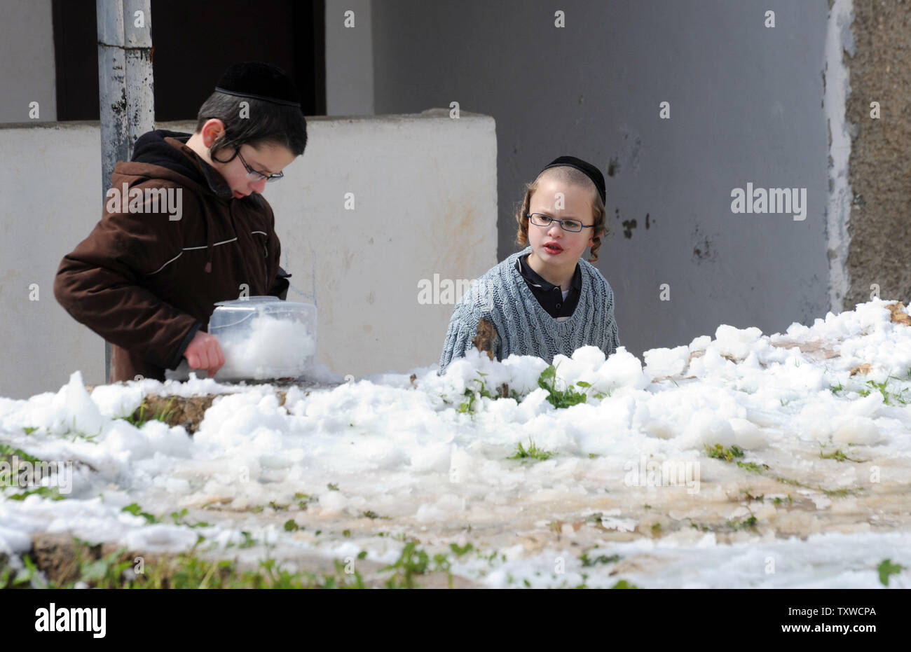 An Israeli boy collects snow in a plastic container after a rare winter snow storm in Jerusalem, March 2, 2012. Residents of Jerusalem woke to 1.575 inches of snow in the first snow fall in Jerusalem in more than two years.  UPI/Debbie Hill - Stock Image