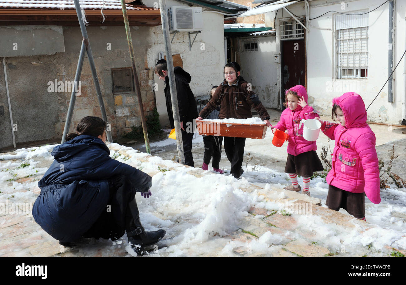 An Israeli boy carries snow to build  a snow man during a rare winter snow storm in Jerusalem, March 2, 2012. Residents of Jerusalem woke to 1.575 inches of snow in the first snow fall in Jerusalem in more than two years.  UPI/Debbie Hill - Stock Image