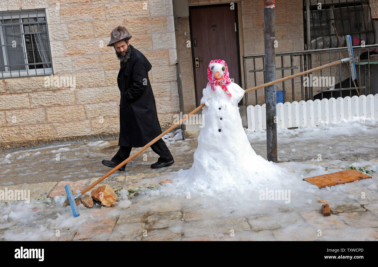 An Ultra-Orthodox Israeli looks at a snow man during a rare winter snow storm in Jerusalem, March 2, 2012. Residents of Jerusalem woke to 1.575 inches of snow in the first snow fall in Jerusalem in more than two years.  UPI/Debbie Hill - Stock Image