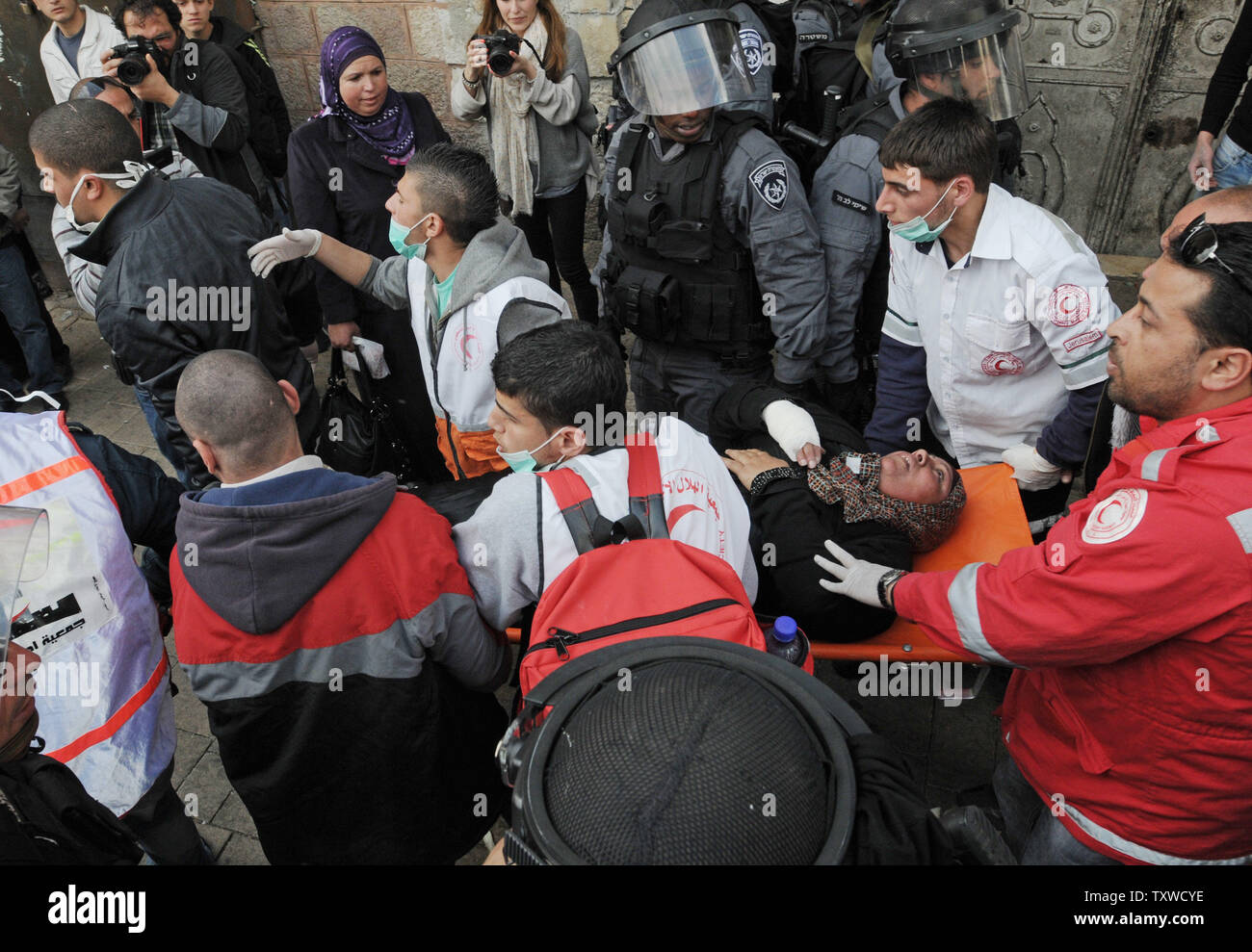 Palestinian medics evacuate a wounded Palestinian protester during a demonstration marking Land Day  near the Damascus Gate in East Jerusalem, March 30, 2012. Palestinians chanted slogans against the Israeli occupation and the continued confiscation of Palestinian land.  UPI/Debbie Hill - Stock Image