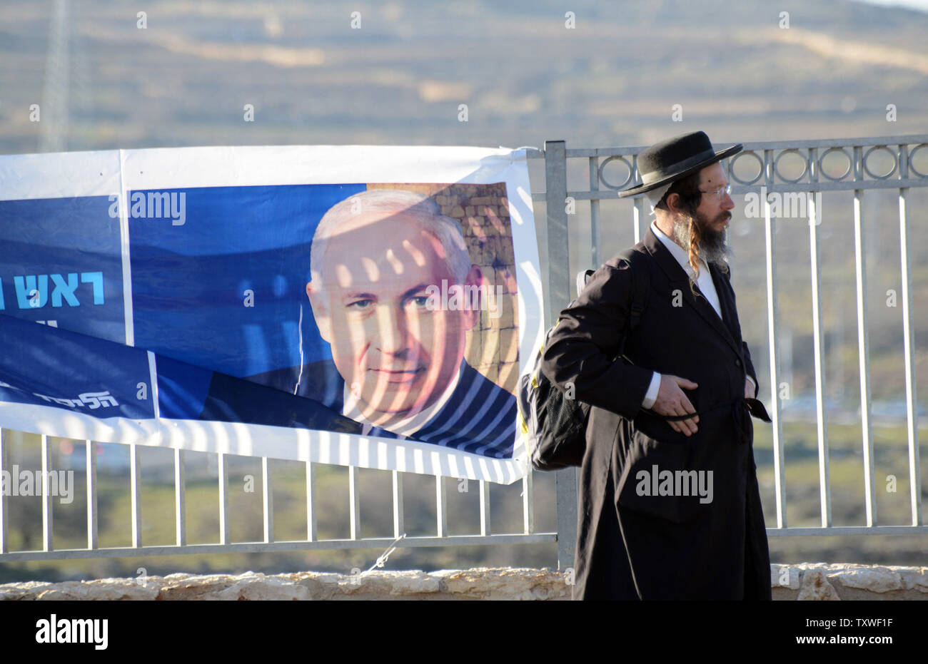 An Ultra-Orthodox Jew stands beside a campaign poster of Israeli Prime Minister and Likud leader Benjamin Netanyahu in the Efrat Settlement in the West Bank, January 20, 2013. Israelis head to vote on Tuesday, January 22, in the general election that  polls predict Netanyahu's Likud-Yisrael Beiteinu ticket to take 32 Knesset seats. UPI/Debbie Hill. - Stock Image