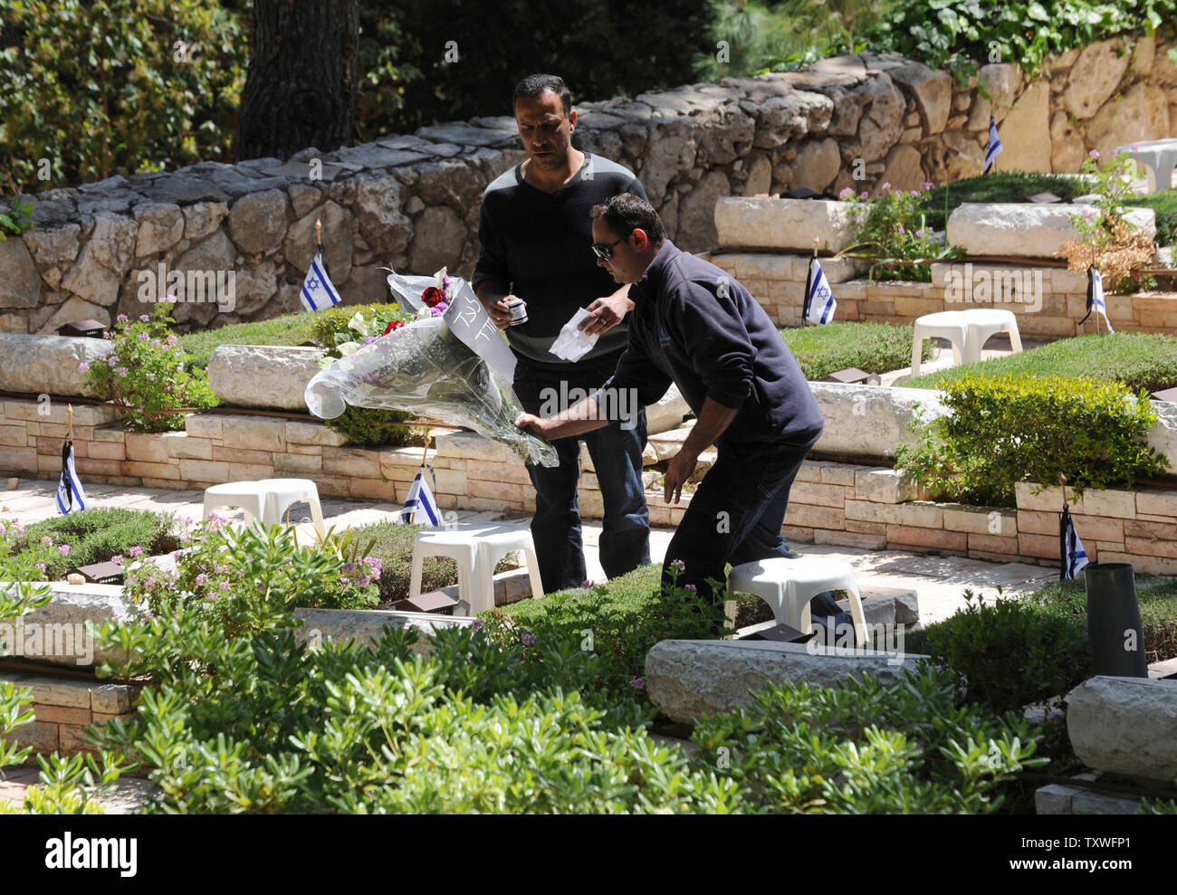 An Israeli places flowers on the grave of a fallen soldier for Remembrance Day at the Mt. Herzl Military Cemetery in Jerusalem, Israel, April 14, 2013. Israel's Remembrance Day for fallen soldiers begins at sunset with a one minute siren.  UPI/Debbie Hill Stock Photo