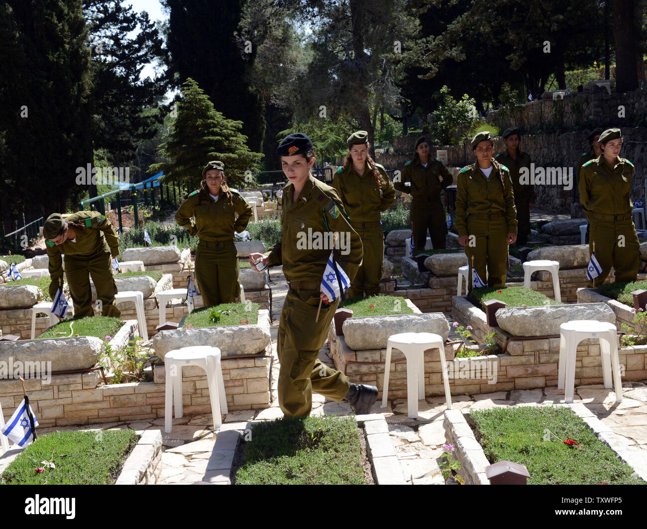 Israeli soldiers decorate the graves of fallen soldiers with national flags with black ribbons for Remembrance Day at the Mt. Herzl Military Cemetery in Jerusalem, Israel, April 14, 2013. Israel's Remembrance Day for fallen soldiers begins at sunset with a one minute siren.  UPI/Debbie Hill Stock Photo