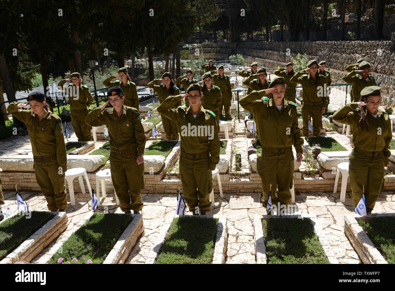 Israeli soldiers salute after decorating graves of fallen soldiers with national flags with black ribbons for Remembrance Day at the Mt. Herzl Military Cemetery in Jerusalem, Israel, April 14, 2013. Israel's Remembrance Day for fallen soldiers begins at sunset with a one minute siren.  UPI/Debbie Hill Stock Photo