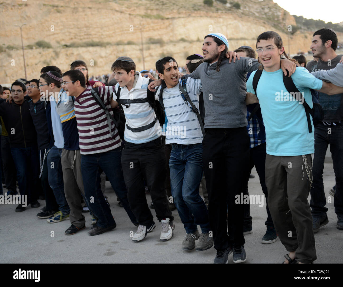 Israeli right-wing settlers chant and dance during a protest calling on the Israeli government to ignore international pressure to freeze settlement building outside the Ma'aleh Adumim Settlement, West Bank,  February 13, 2014. The settlers marched to the unbuilt E1 area in the West Bank and demanded that the state build Jewish settlements in the contested area.UPI/Debbie Hill Stock Photo