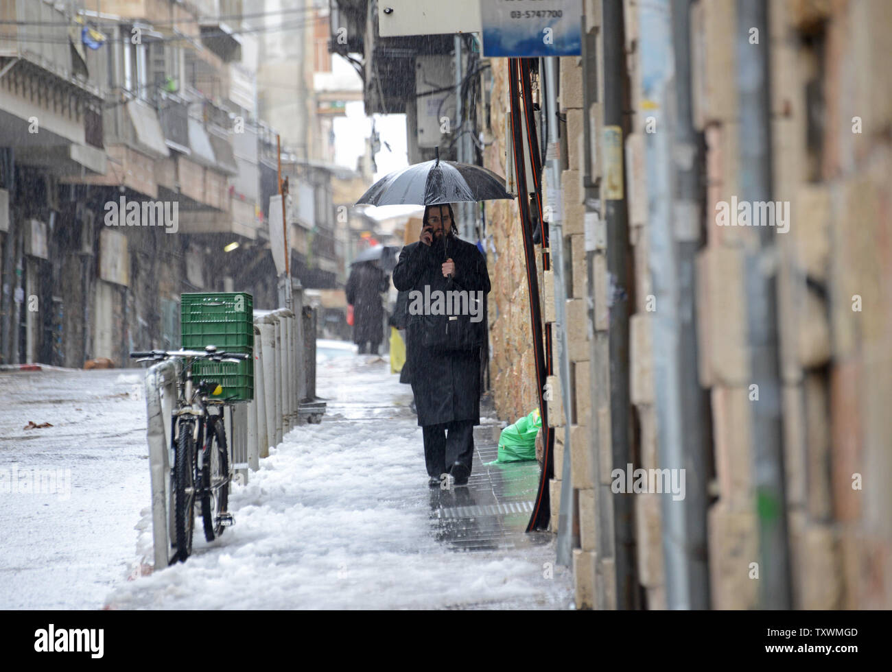 An Ultra-Orthodox Jew talks on a cellphone while walking in the snow and rain during a winter storm in Jerusalem, Israel, January 8, 2015.  A heavy winter storm is hitting the Middle East, while only 5 cm. or 1 inch of snow fell in Jerusalem. UPI/Debbie Hill Stock Photo